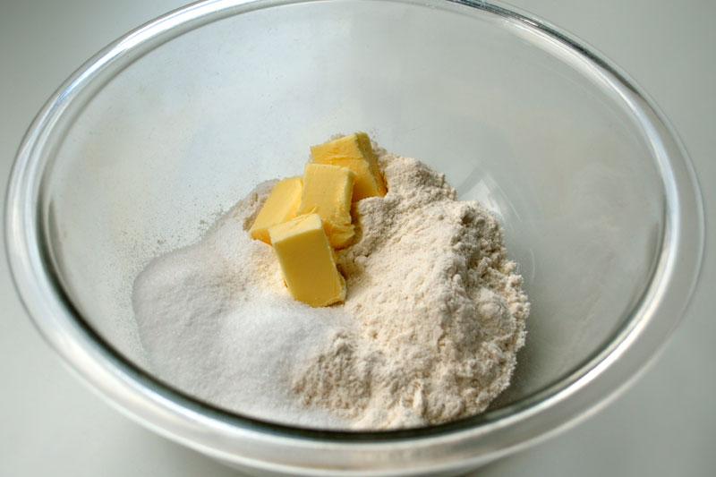 Passo 1: Comece a receita pesando todos os ingredientes secos numa balança para uso culinário. Coloque 25g de açúcar, 150g de farinha de trigo, 5g de fermento em pó numa vasilha junto com 30g de manteiga, que precisa estar bem mole.