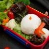 Monte os bolinhos de arroz para criar o boneco de neve. O cachecol pode ser feito com salsicha e o nariz, com cenoura