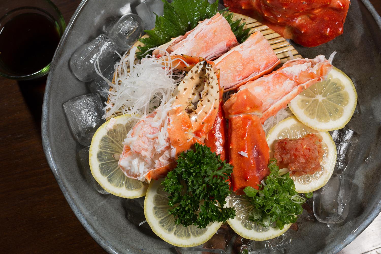 Sashimi de centolla servido com yuzu ponzu, momiji oroshi e cebolinha